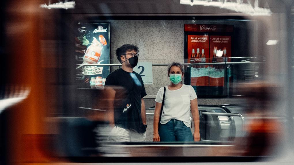 Menschen mit Maske an einer U-Bahn-Station