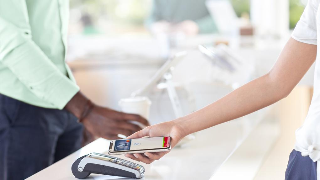 Junge Frau bezahlt ihren Einkauf mit Apple Pay